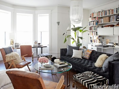 Nate Berkus turns the stark space into an inviting multipurpose room. Creating a focal point and a plush sofa.