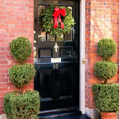 Classic. Black door, red ribbon, and topiaries.
